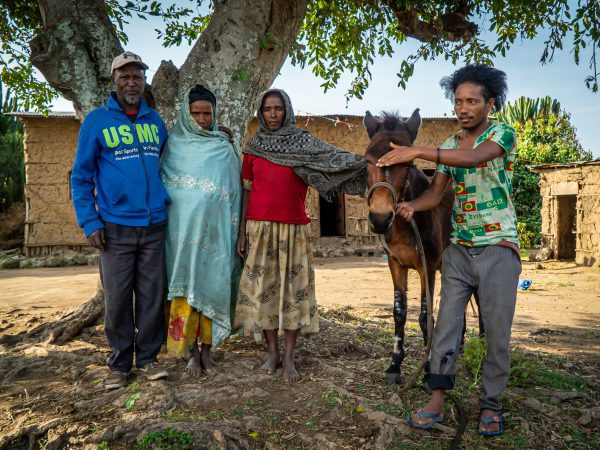 A family stands with their mule outside of their home in Ethiopia.
